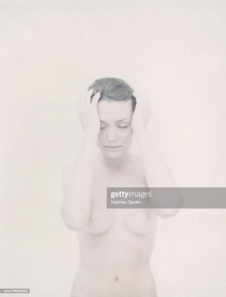 Nude woman holding head, eyes closed, portrait. : Bildbanksbilder