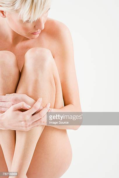 Nude woman hugging her legs