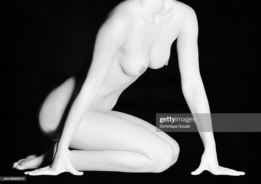 Nude woman kneeling, chest up, hands to floor. : Stockfoto