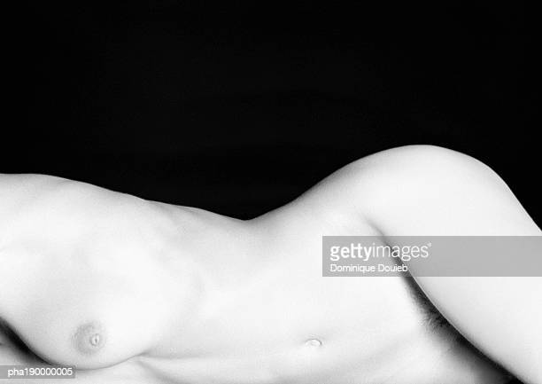 Nude woman laying, mid-section.