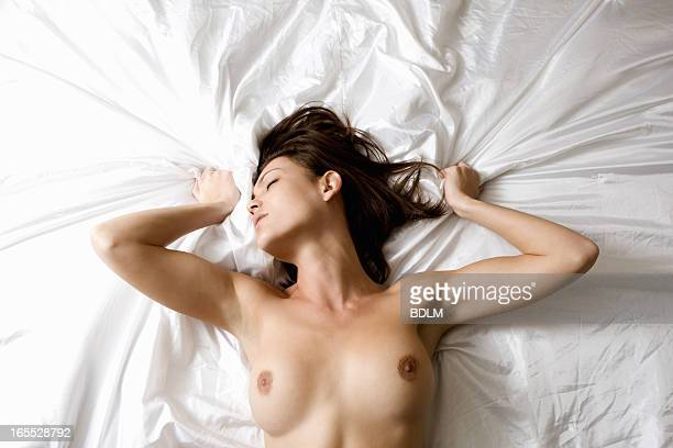 Nude woman laying on bed