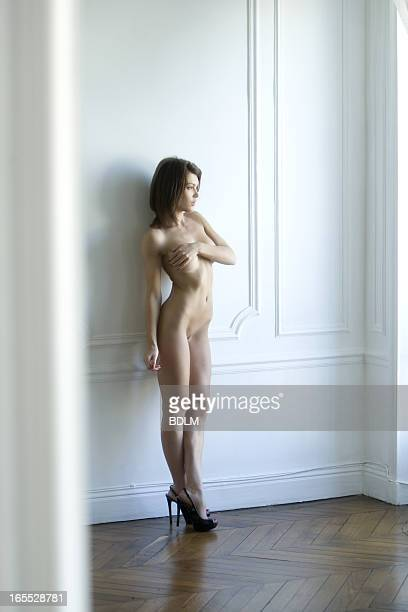 Nude woman leaning against wall
