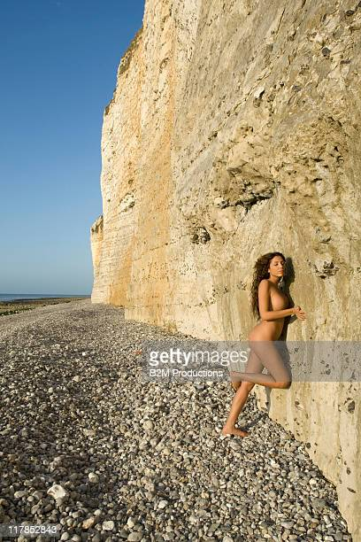 Nude woman leaning by rock on beach