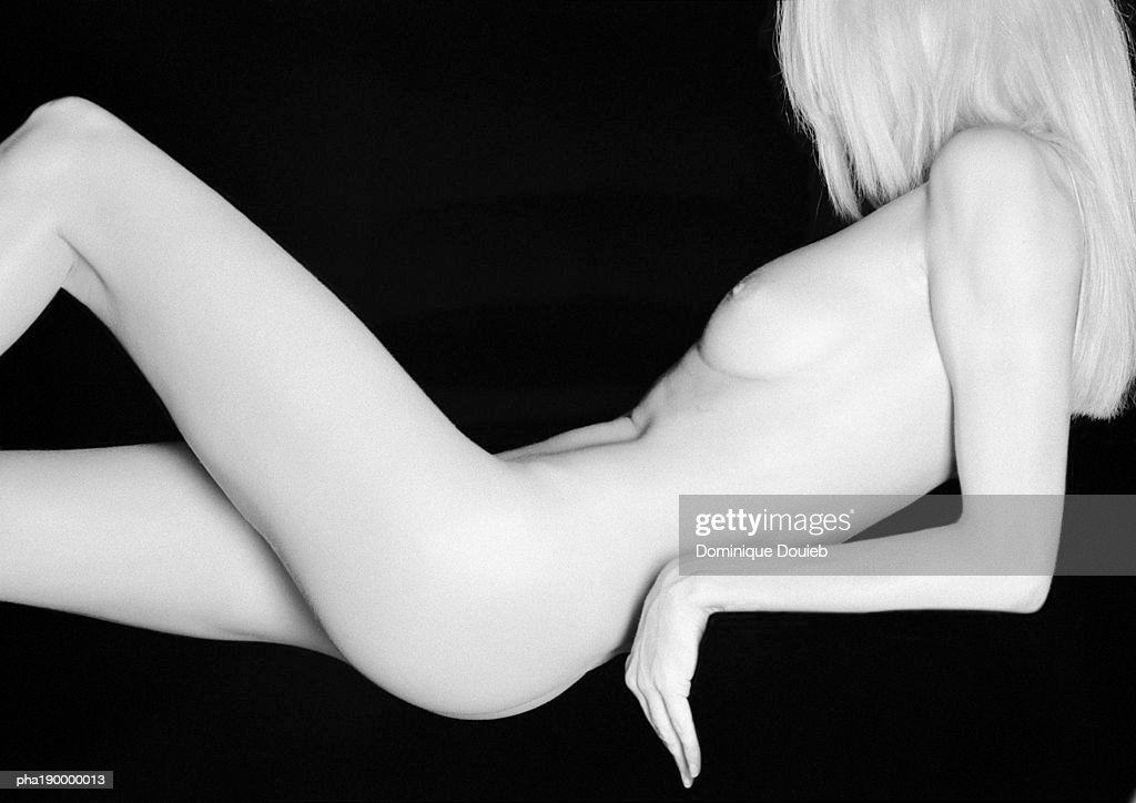 Nude woman leaning on elbows, knee up, mid-section. : Stockfoto