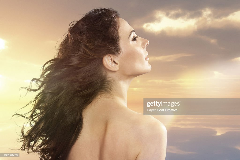 nude woman looking toward the colorful sunset : Stock Photo