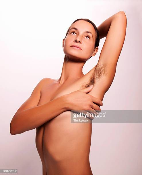 a nude woman looking up covers her breast with her hand. - armpit hair woman stock pictures, royalty-free photos & images