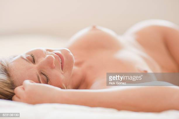 Nude woman lying in bed