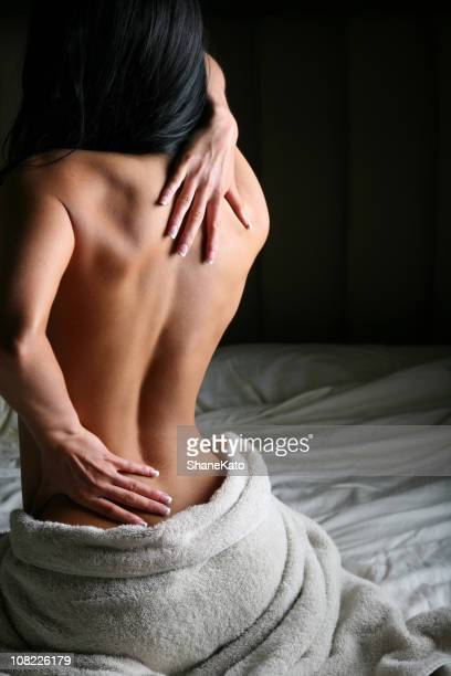 nude woman massaging her back muscles with painful backache - sensual massage stock photos and pictures