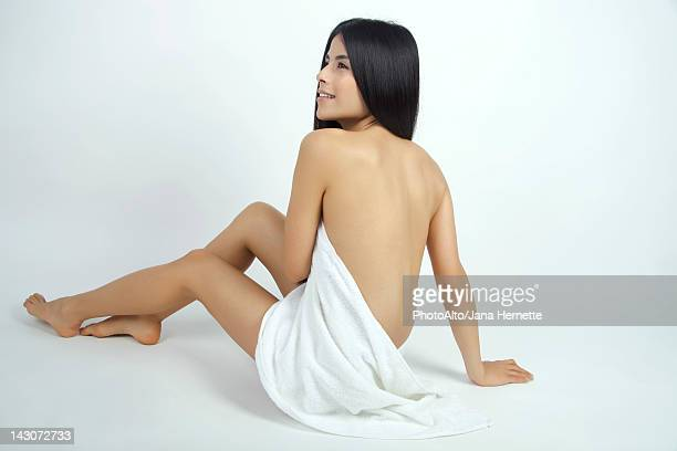 Nude woman partially covered with towel, rear view