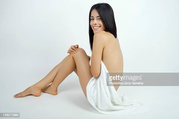 Nude woman partially covered with towel, smiling over her shoulder at camera