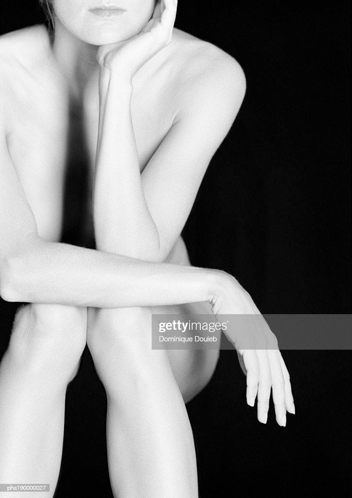 Nude woman sitting, arm crossed over legs. : Stockfoto