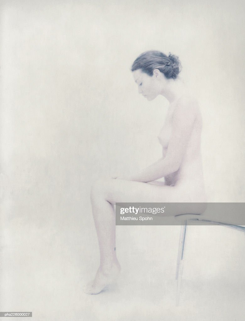 Nude woman sitting at end of chair, side view. : Stockfoto