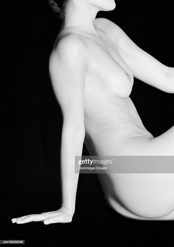 Nude woman sitting, hand to floor, side view. : Stockfoto