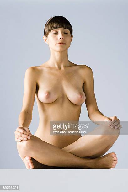 nude woman sitting in lotus position, eyes closed - nudista fotografías e imágenes de stock