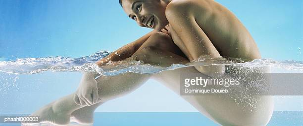 nude woman sitting in water, side view - skinny dipping - fotografias e filmes do acervo