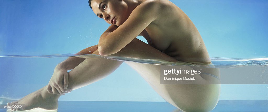 Nude woman sitting in water, side view : Stockfoto