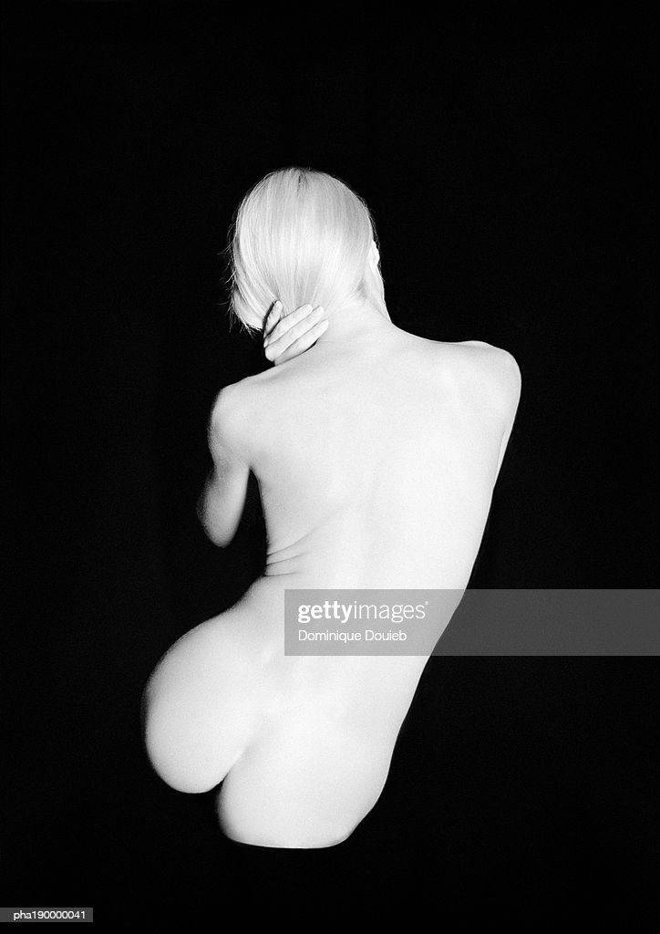 Nude woman sitting, leaning right, rear view. : Stockfoto