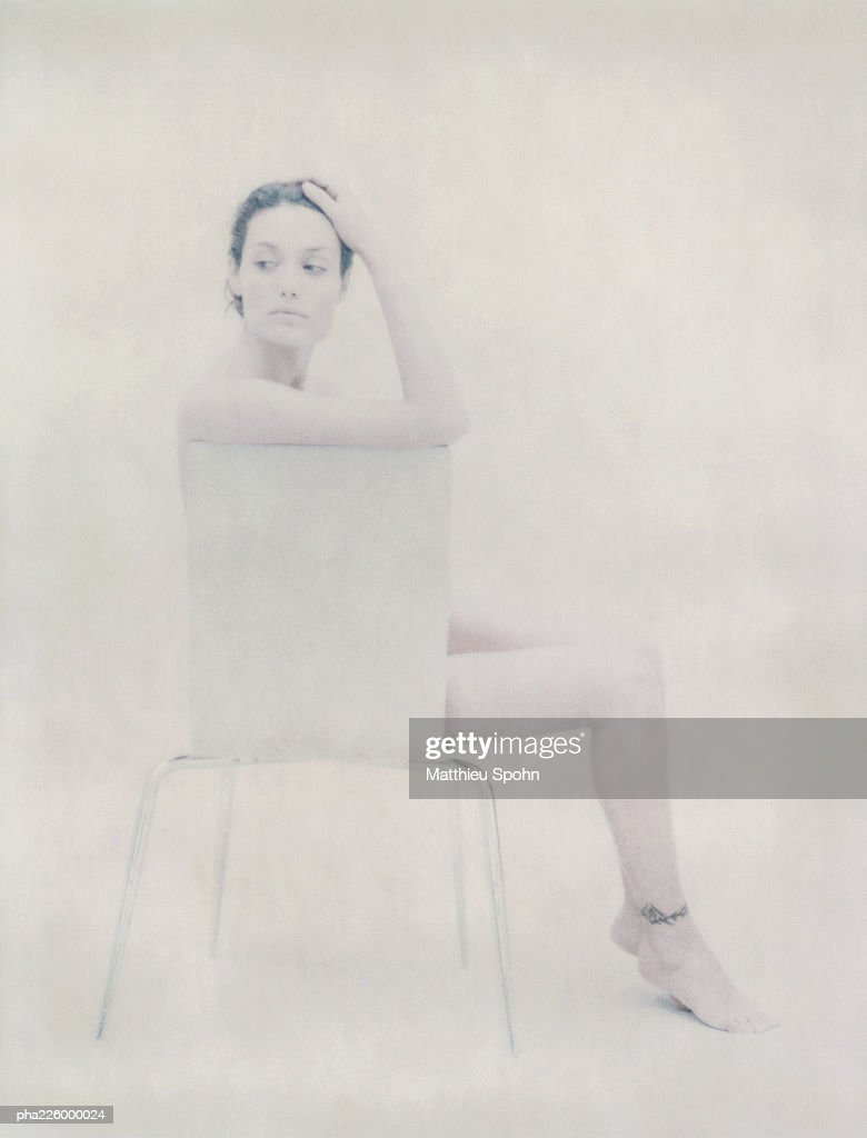 Nude woman sitting on chair, side view. : Stockfoto