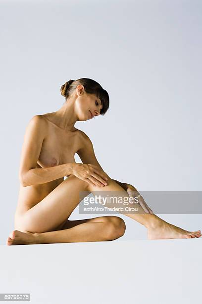 Nude woman sitting on floor touching leg