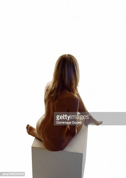Nude woman sitting, rear view