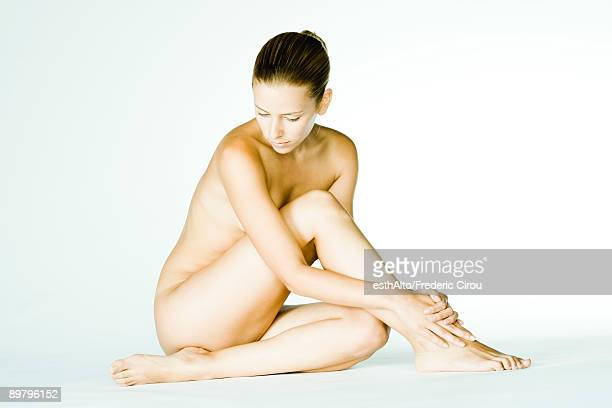 Nude woman sitting with hands on ankle, head down
