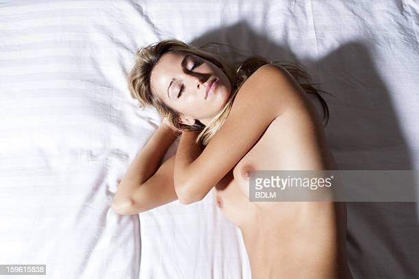 Nude woman sleeping on bed