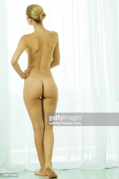 Nude woman standing by curtained window, full length