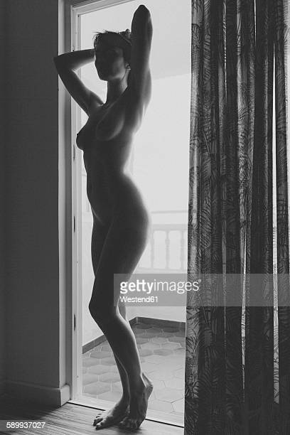 Nude woman standing in balcony door frame