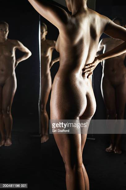 Nude woman standing in front of mirrors