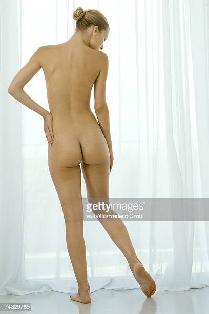 Nude woman standing in front of window, looking down, rear view