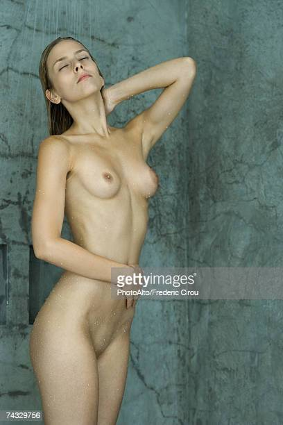 Nude woman standing in shower, eyes closed