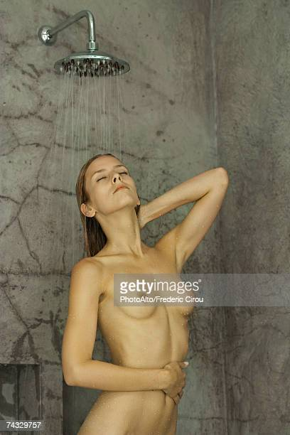Nude woman standing in shower, eyes closed, waist up