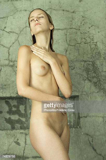 Nude woman standing in shower, touching chest, eyes closed