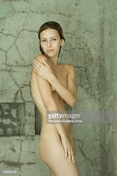 Nude woman standing in shower, touching shoulder, looking at camera