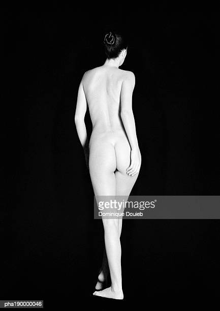 Nude woman standing, rear view.