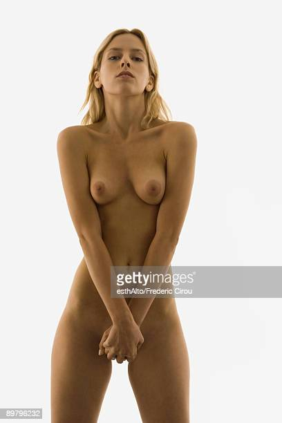 Nude woman standing with hands clasped over groin, looking at camera