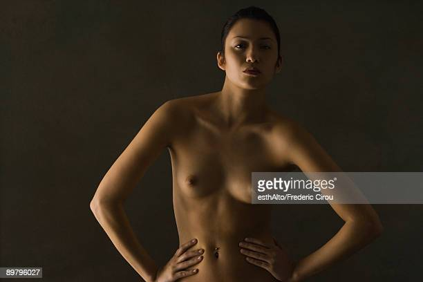 nude woman standing with hands on hips, staring at camera - clair obscur photos et images de collection