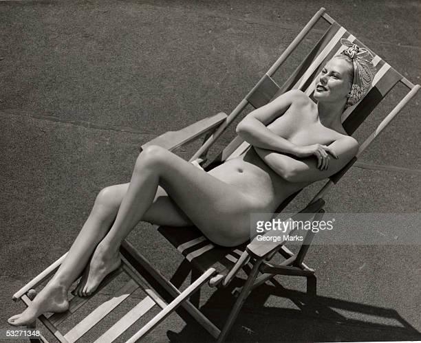 nude woman sunbathing in beach chair - nudista fotografías e imágenes de stock