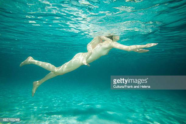 Nude woman swimming with toddler on back