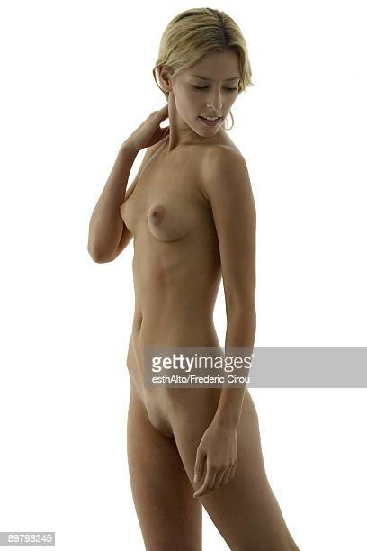 Nude woman touching neck, looking over shoulder