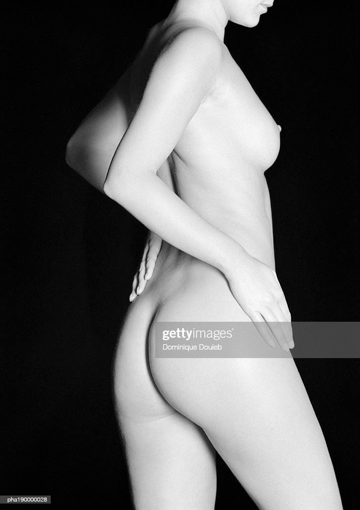 Nude woman, twisting from the hips, rear view. : Stockfoto