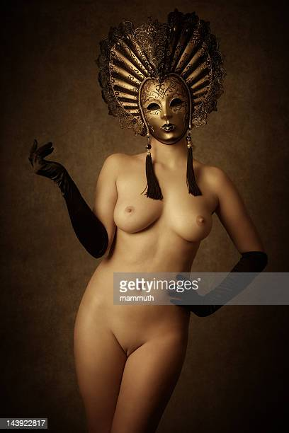 nude woman wearing golden venetian mask - dressed undressed women stockfoto's en -beelden