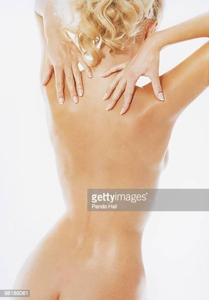 nude woman with hands on back, rear view - massaggio sensuale foto e immagini stock