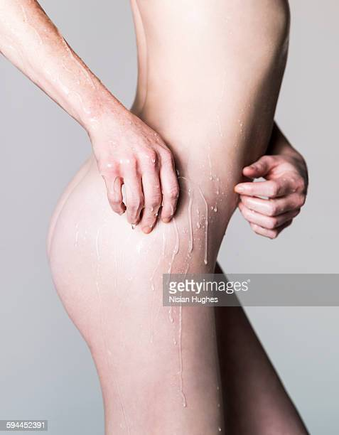 nude woman with oil dripping off arm - beautiful bare bottoms stock pictures, royalty-free photos & images