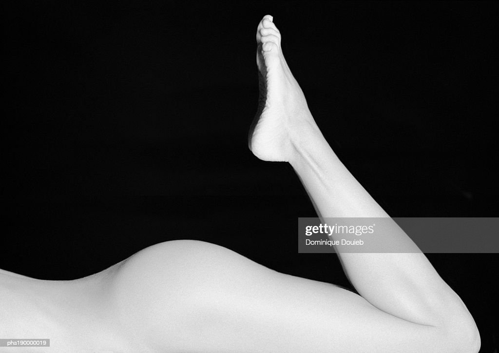Nude woman's buttocks, legs raised. : Stockfoto
