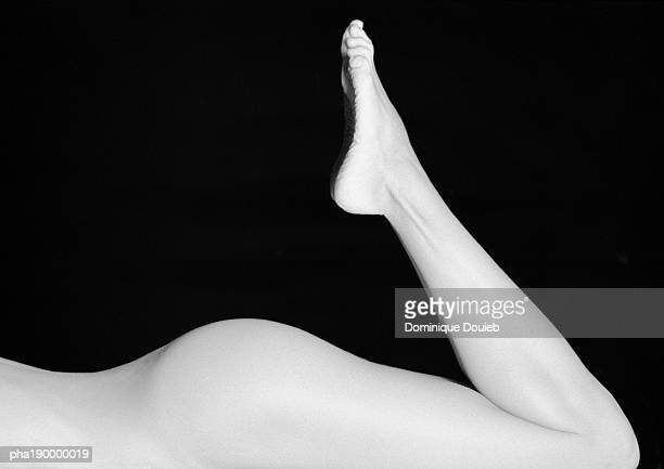 nude woman's buttocks, legs raised. - female bare bottoms stock photos and pictures