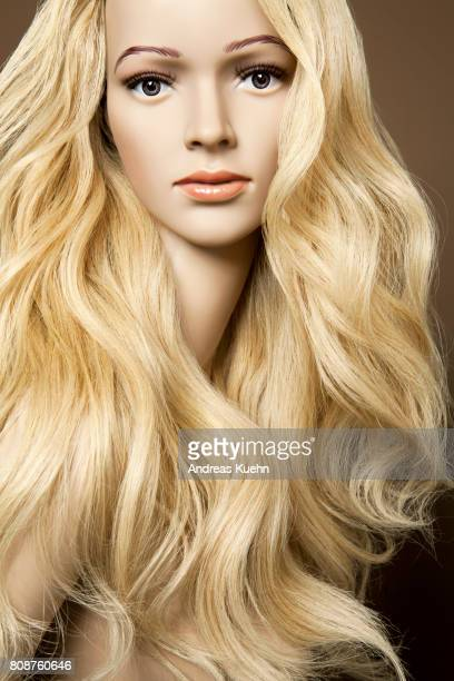 Nude, young female mannequin with a long, wavy, blond human hair wig and pale skin, portrait.