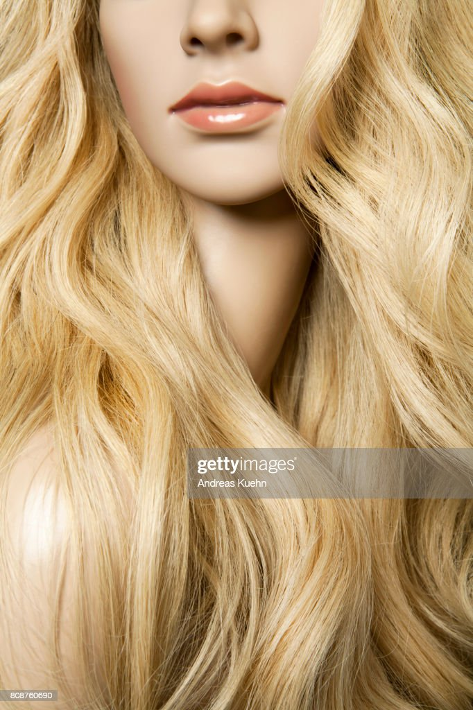 Nude young female mannequin with a long, wavy, blond human hair wig and pale