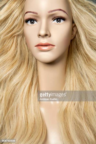 Nude, young female mannequin with a long, wavy, blond, human hair wig and pale skin, portrait.