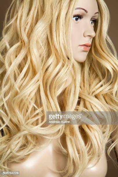 Nude, young female mannequin with a long, wavy, blond human hair wig and pale skin in front of a brown background in a profile position, portrait.